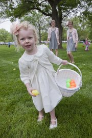 Julietta Keathley-Helms gathers up a basket of eggs during the Egg Hunt Extravaganza on Saturday in South Park. In background watching are her older sisters, twins Liliana and Ella, 11, all of Lawrence.