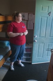 Office assistant Pamela Gates stands inside a room that a family of four shares at The Salvation Army Family Service Center in Olathe. A set of bunk beds is just a few feet inside the door of the one-room unit.