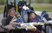 A little rain doesn't disrupt vendor Cindy Roberts, above, her dog P.J. and her step-daughter Riley Wilson, 6, as they sell T-shirts at the first Lawrence Flea market of the season on April 7 at Teepee Junction.