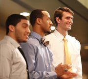 Kansas center Jeff Withey smiles as he is recognized before those gathered during the Men&#39;s Basketball Banquet on Monday, April 9, 2012 at the Holidome. Also pictured are Niko Roberts, left, and Travis Releford.