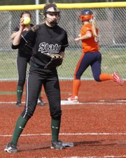 Free State pitcher Meredith Morris fields a ground ball but can't make a play on the Olathe East batter, safe at first, or a Hawks runner advancing to second, background, on Tuesday at FSHS.