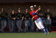 Kansas third baseman Jordan Dreiling throws a runner out at first base while players in the Wichita State dugout watch on Tuesday, April 10, 2012 at Hoglund Ballpark.