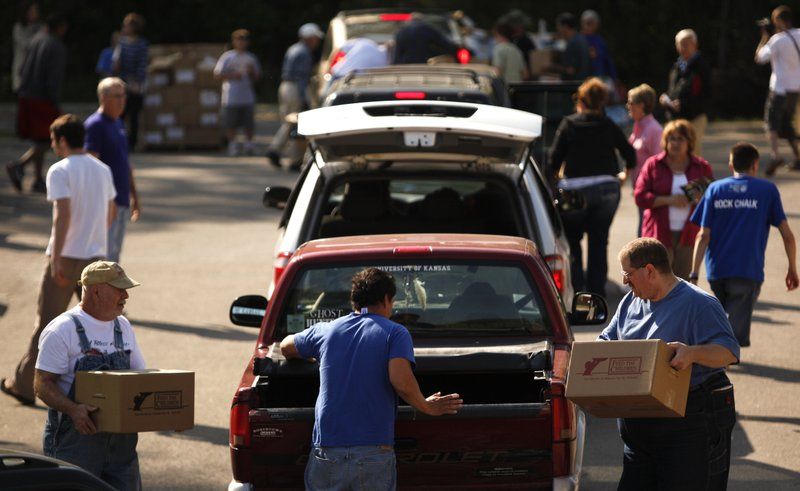 Volunteers Gene Gibson, front left, and William Chapman, front right, bring boxes of food and personal care items to the back of a truck as cars file into line during a Feed The Children distribution on Wednesday, April 11, 2012, in the parking lot of Just Food, 1000 E. 11th St. Feed The Children delivered two semi tractor-trailers full of supplies that were designed to help 800 Douglas County families for one week. About 350 families picked up a donation Wednesday.