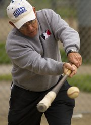 Former Lawrence High School baseball coach Ron Garvin hits balls to players so they can practice fielding  during a little league baseball practice Saturday, April 7, 2012 at the YSI sports complex. Garvin helps coach his grandson's baseball team.
