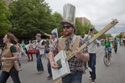 Members of a make-shift and recycled string band, representing the Community Mercantile, march and perform Saturday, April 14, 2012 during the Earth Day parade.