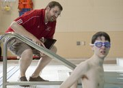 Danny Lenz, local program director for Douglas County Special Olympics, left, gives some instructions to swimmer Ben Clark, 18, during training at the Lawrence Indoor Aquatic Center Saturday, April 14, 2012.