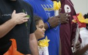 Nine-year-old Aris Grady listens to the national anthem while holding her Olympic torch during the Quail Run Girl Scouts' annual father-daughter event Sunday.