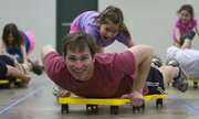 Seven-year-old Caroline Bork pushes her father, Reid, on a scooter as the two compete in the Scooter Swimming event during the Quail Run Girl Scouts' annual father-daughter event on Sunday in Building 21 at the Douglas County Fairgrounds. The theme of this year's event was the Olympics.