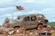 A tattered American flag flies over a vehicle where two young girls ages 5 and 7 were found after a severe thunderstorm spawned a massive tornado at Hideaway Mobile Home Villa in Woodward, Oklahoma shortly after midnight Sunday, April 15, 2012. The girls, Faith and Kelley Hobbie, ages 5 and 7, and their father, Frank Hobbie, were three of the five fatalities in the Northwest Oklahoma destruction.