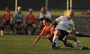 Lawrence High senior defender Lauren Fleming and Olathe East senior Sophia Bachman get tangled up during the first half on Tuesday, April 17, 2012 at LHS.