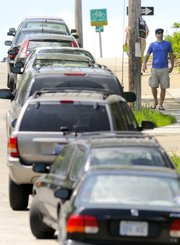 "Kansas University senior Garrett Page walks down the hill from campus Tuesday on 12th Street, past a line of parked cars. City commissioners on Tuesday approved new regulations aimed at decreasing parking congestion in the Oread neighborhood. Page, who lives near the corner of 12th and Ohio streets, said from experience, ""If you want to go anywhere in the Oread neighborhood, you may as well just walk."""