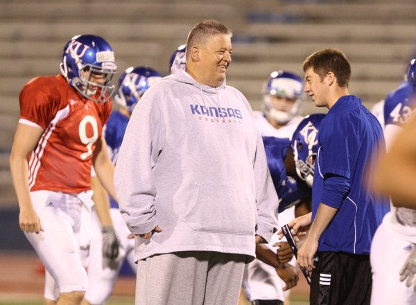 Kansas head coach Charlie Weis laughs with his son Charlie Weis Jr. during a morning practice on Thursday, April 19, 2012 at Memorial Stadium.