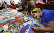 Middle school students Sara Galloway, front, and Lydia Caldwell work with other classmates on detailing a quilt-style homage to Harlem Renaissance artist Aaron Douglas Wednesday at Liberty Memorial Central Middle School. Seventeen students in the class are collaborating on the piece with quilt artist Marla Jackson. Plans are for the quilt to be displayed at Kansas Universitys Spencer Museum of Art at the end of July.