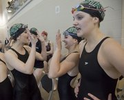 From left, Free State High swimmers Caroline King, Katie Kimbrough and Hana Arch cheer on teammate freshman Alexa Mailk during the girls 200-yard medley relay at the Free State Tri swim meet Friday, April 20, 2012, at FSHS. It was also senior night for the Firebird swimmers.