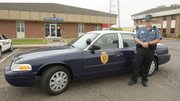 In this April 5, 2012 photo, Kansas Highway Patrol trooper Matt Mullen stands by the new retro patrol car at their headquarters in Wichita, Kan. Trooper Matt Mullen, who is based in Wichita, said he has been getting quizzical looks from children and second glances from adults since being assigned one of the retro 2011 Crown Victoria models.