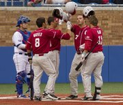 Oklahoma players celebrate Max White's (7) three run home run at the plate in front of Kansas catcher James Stanfield during the second game of Kansas' three game series against Oklahoma April 28, 2012 at Hoglund Ballpark.
