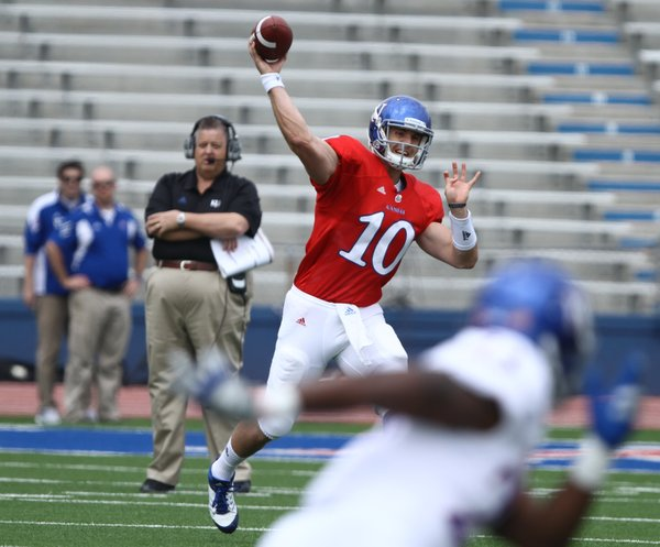 Kansas quarterback Dayne Crist pulls back to throw on his first play from scrimmage during the Spring Game on Saturday, April 28, 2012 at Kivisto Field. In back, head coach Charlie Weis looks on.