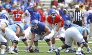 Kansas quarterback Dayne Crist calls out a play from behind offensive lineman Trevor Marrongelli during the first half of the Spring Game on Saturday, April 28, 2012 at Kivisto Field.