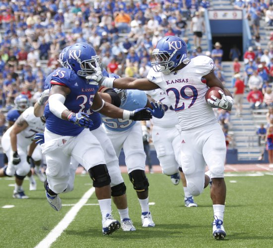 Kansas running back James Sims tries to stiff arm defensive end Toben Opurum during the second half of the Spring Game on Saturday, April 28, 2012 at Kivisto Field.