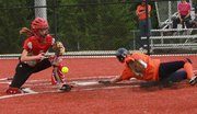 Lawrence High catcher Kassidy Husted loses the ball as she gets ready to tag Olathe East's Allison Stewart on Tuesday, May 1, 2012, at LHS.