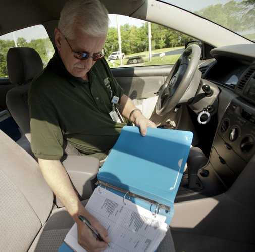 Michael Van Pelt, a Lawrence Memorial Hospital lab courier, records deliveries in his log book on his route, Wednesday, May 2, 2012. Van Pelt is grateful for the financial and emotional support he received from his colleagues while battling cancer last year. He received $700 from the annual LMH Employee Campaign in addition to gift certificates for a holiday meal and presents for his family.
