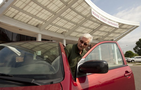Michael Van Pelt, a lab courier for Lawrence Memorial Hospital, squeezes into his car after delivering samples from the Douglas County Jail to the LMH lab on Wednesday, May 2, 2012. Van Pelt was a beneficiary of the hospital's annual Employee Campaign when he was undergoing treatment for head and neck cancer.