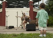 Two-year-old Liam Sturm watches Nicolette Paige perform. Art in the Park featured art, music, food and a concurrent flying disc competition for dogs.