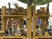 Cynthia Schmidt, Paola, places a vase on a display shelf as she sets up her booth at Art in the Park. Cloudy skies threatened rain all day, but the downpour held off until the event's closing time.