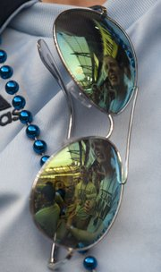 Members of the Mass Street Mob are reflected in a pair of sunglasses during the Sporting KC match against Montreal Saturday, May 5, 2012.