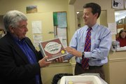 From left, Lawrence Community Shelter director Loring Henderson, accepts some Kansas steak burgers from  Gov. Sam Brownback. Brownback delivered  120 steak burgers to the shelter on Tuesday, May 8, 2012, as part of a Final Four bet he made with Kentucky Gov. Steve Beshear.