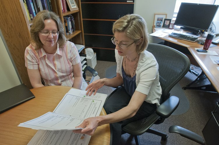 Jill Sittenauer, left, regional communications director for the American Cancer Society, visits with researcher Christie Befort, of Preventive Medicine & Public Health at Kansas University Medical Center, on May 3, 2012, in Befort's office. The American Cancer Society helped fund Befort's pilot weight loss study for rural breast cancer survivors, and Befort is showing Sittenhauer some of those promising results. Befort said women who are overweight and women who gain weight after diagnosis have an increased risk for breast cancer recurrence and worse prognosis compared to women with a normal body weight.