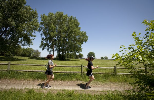 Lawrence residents Lori White, left, and Ricki Endsley take off around a turn as they run on the north river trails on Thursday, May 10, 2012.