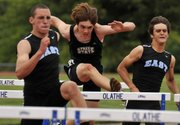 Free State&#39;s Alex Heath, center, vaults up and over in the boys 100 meter hurdles Friday, May 11, 2012, during the Sunflower League track meet at the Olathe District Activity Center in Olathe.