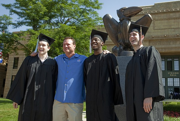 From left, KU basketball senior Jordan Juenemann, coach Bill Self, and players Tyshawn Taylor and Conner Teahan gather for a photograph before Sunday's KU commencement at Memorial Stadium.