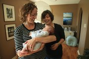 Doula Lindsay Clements, left, holds 5-week-old Elsa Warnock on Wednesday as her mother Sara Warnock looks on. Clements was Warnock's doula during pregnancy and labor.