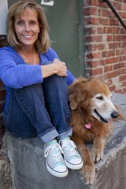 Susan Stuever shows off one pair of her Converse shoes with her dog Wednesday.