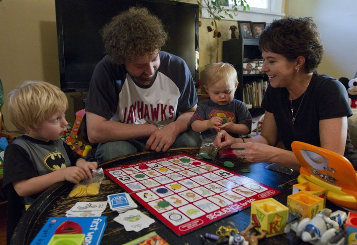 Eudora residents Aman and Laura Reaka play a game of Sequence with 3-year-old Kayden and 17-month-old Eric at their home on May 17, 2012. Aman and Laura adopted Kayden after becoming foster parents and are in the process of also adopting Eric.