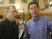 Gov. Sam Brownback speaks with state Rep. Mitch Holmes, R-St. John, on Saturday.