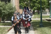 Baker University business professor Martha Harris carries the university's mace Sunday as she leads the Kansas City St. Andrew Pipes and Drums, and Baker's undergraduate class of 2012, on a procession through campus to commencement ceremonies at the George F. Collins Center.