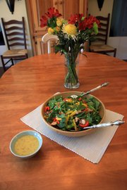 Ivy Travis' mother-in-law's spinach salad uses fresh spinach, sweet peppers, mushrooms, bacon, and finishing off with a mustard vinegar based dressing.
