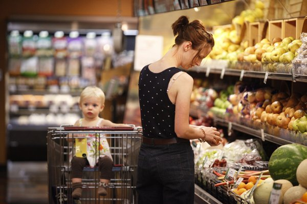Megan Hemphill, Lawrence, browses the selection of fruit as she shops for groceries with her daughter, Lena, on Tuesday, May 22, 2012, at The Merc, 901 Iowa.
