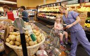 Lawrence resident Liz Black lays some potatoes in her cart as she shops with her 2-year-old daughter Arie on Tuesday, May 22, 2012, at The Merc, 901 Iowa.