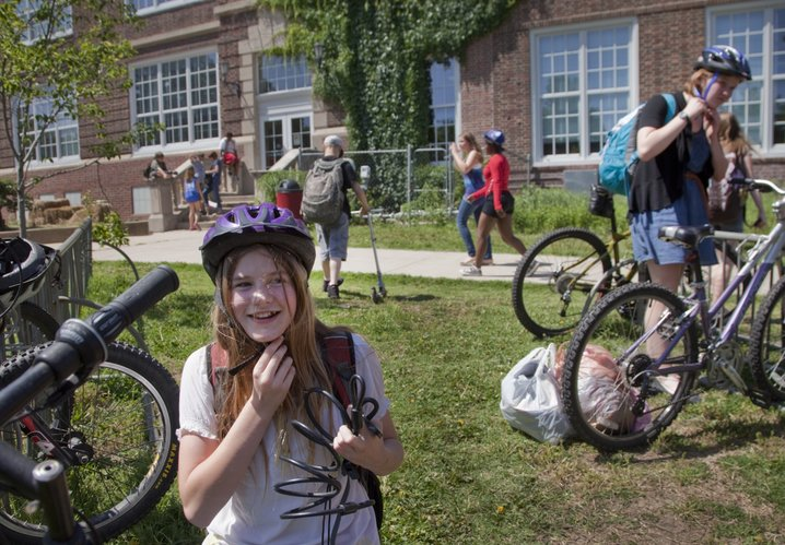 Liberty Memorial Central Middle School students Eleanor Matheis, 13, foreground left, and Mary Reed Weston, 13, right, put on their helmets before bicycling home from school Tuesday, May 22 2012. Kansas has the 27th highest rate of injury-related deaths in the country, according to a new report. Kansas does not require children to wear helmets, but Lawrence has passed an ordinance requiring children, ages 16 and under, to wear a helmet, but doesn't enforce