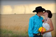 In this May 19, 2012, photo provided by Cate Eighmey, Caleb & Candra Pence pose for a wedding photo as a tornado swirls in the background after they were married in Harper County, Kan.