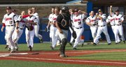 Lawrence High catcher Drew Green walks to the mound as Blue Valley West celebrates the game-winning run in the first round of the Class 6A state tournament Friday, May 25, 2012, at Hoglund Ballpark.