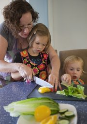 Kris Adair helps her daughter Audrey Montgomery, 4, cut a pepper for a Salad on a Stick. Audrey&#39;s sister Maurene Montgomery, 2, helps at right.
