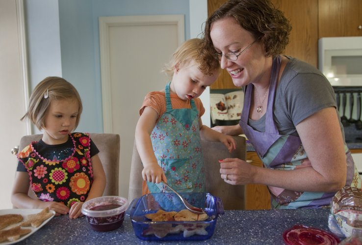 Maurene Montgomery, 2, center, pours a fruit sauce on a fruit bread pudding dish she was helping her sister Audrey, 4, left and her mother Kris Adair, prepare at their home, Friday, June 1, 2012.