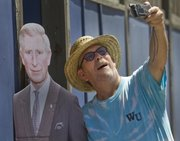Paul Goebel, of Lawrence, snaps a photograph of himself with a cardboard cutout of Prince Charles on Saturday during the celebration.