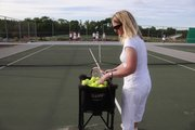 Kirsty Elliott, a Lawrence tennis instructor, serves up some tennis balls at Free State High School.  The school district's new plan would put in tennis lights at Free State High School.