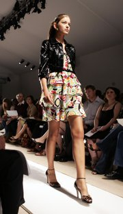 A model wears a lacquered cropped jacket over a modernist print top and skirt at Cynthia Steffe's spring 2006 collection during Fashion Week in New York, Monday Sept. 12, 2005. Wear a cropped jacket or blazer to a summer wedding if you don't want to bare your arms.